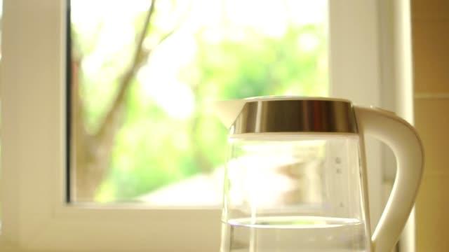 una teiera trasparente con spalti d'acqua sul tavolo della cucina. il processo di acqua bollente contro un tramonto che brilla attraverso una finestra. il concetto di pausa caffè e la fine della giornata. - teiera video stock e b–roll