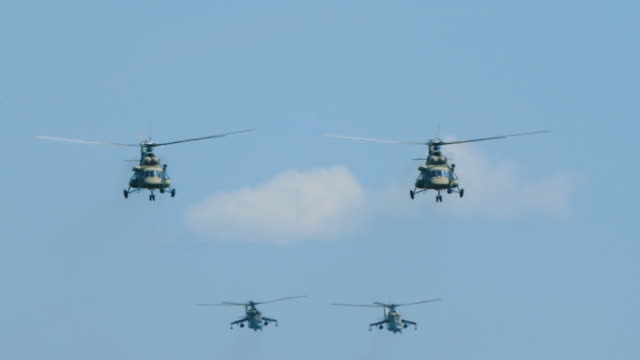 Transport and combat helicopters fly to war in slow motion, preparing for battle