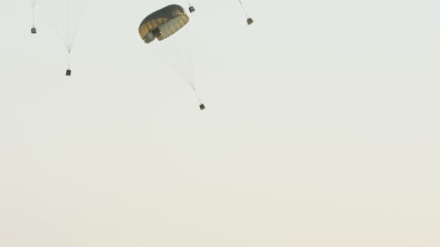 vídeos de stock, filmes e b-roll de avião de transporte c-130 caindo pacotes de carga com para-quedas - paraquedismo