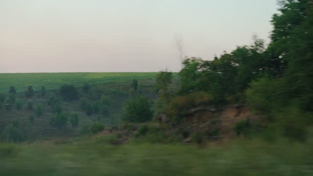 Transport, travel, road, railway, landscape, comnication, Agriculture concept - view from window of speed train on landscape of beautiful nature green field and forest in sunny clear summer sunset