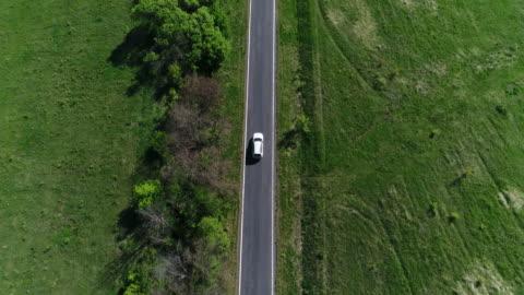 vídeos de stock e filmes b-roll de 4k transportation aerial view white car driving on countryside road - cena rural