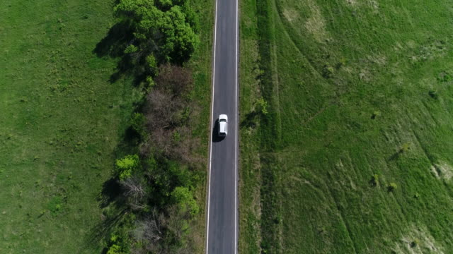 4k transportation aerial view white car driving on countryside road - viaggio su strada video stock e b–roll