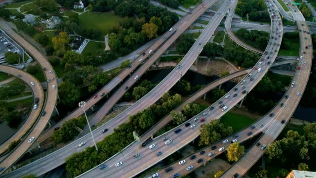 transport highway mega sigvägvägen resa destination antenn drönarvy ner på vägarna på rush hour houston, texas drone flygfoto på sunrise - motorväg bildbanksvideor och videomaterial från bakom kulisserna
