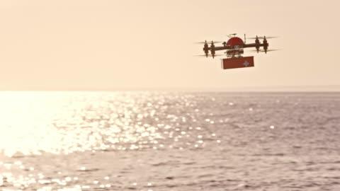 slo mo uav che trasporta il kit di pronto soccorso sopra il mare - drone video stock e b–roll