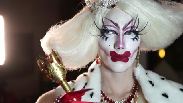 stockvideo's en b-roll-footage met transseksueel man met make-up in rode jurk zitten in kleedkamer - drag queen