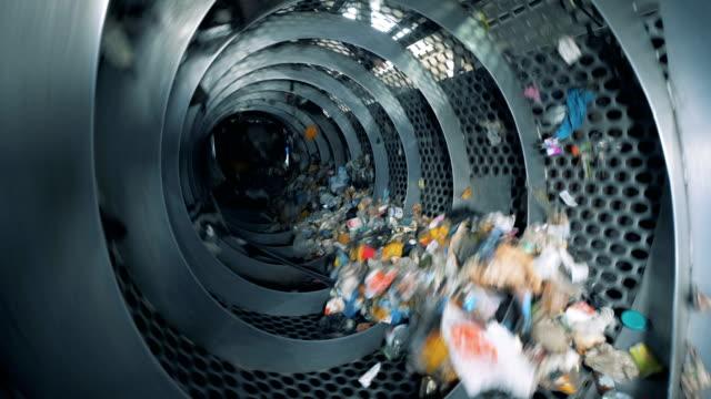 trash is revolving inside an industrial recycling machine. waste recycling equipment. - odzyskiwanie i przetwarzanie surowców wtórnych filmów i materiałów b-roll