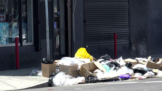 trash piled on a city sidewalk - marciapiede video stock e b–roll