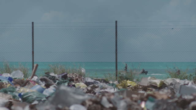 Trash site on tropical island. Garbage piles against the turquoise waters of a tropical ocean. pacific islands stock videos & royalty-free footage