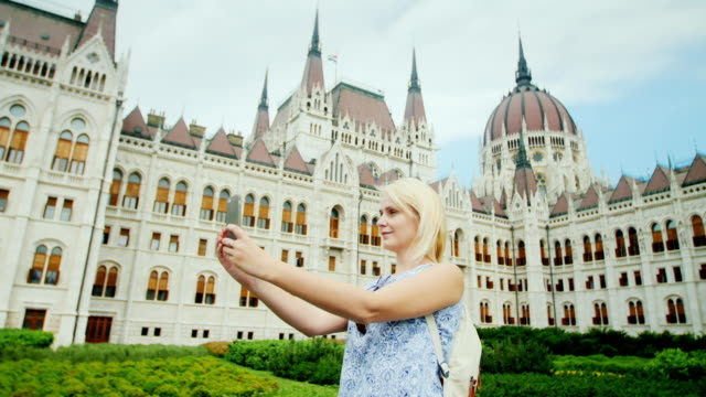 Travel around Europe - a tourist does selfie on the background of the Hungarian Parliament in Budapest video