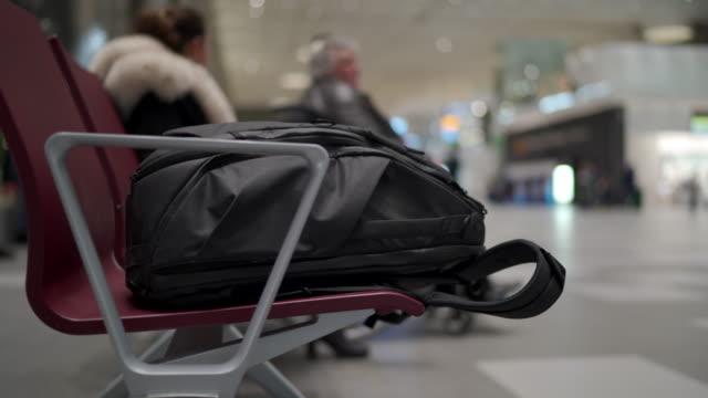 stockvideo's en b-roll-footage met de rugzak van de reis op bank bij de wachtende ruimte van de luchthaventerminal met stoelen - vliegveld vertrekhal