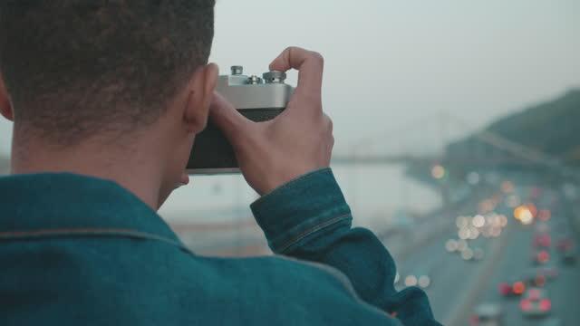 Travel blogger taking photo of cityscape, using old fashioned camera, vintage