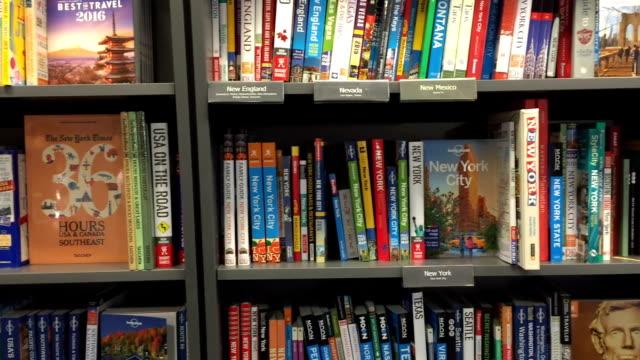 stockvideo's en b-roll-footage met reisboeken in een boekhandel of bibliotheek - boekenkast