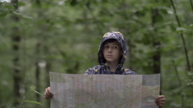 travel boy in the forest looks at the map, rainy weather