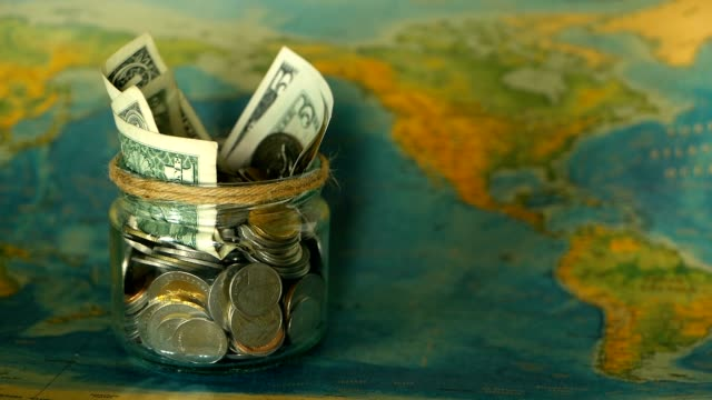 Travel budget concept. Money saved for vacation in glass jar on world map background Travel budget concept. Money saved for vacation in glass jar on world map background, copy space. Banknotes and coins for adventure. Savings for journey. Collecting money for trip. Moneybox with cash. international match stock videos & royalty-free footage