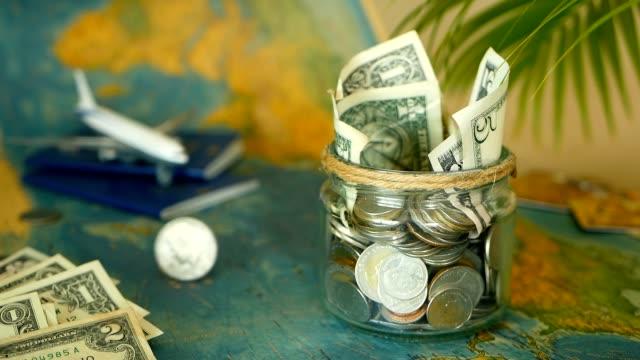 vídeos de stock e filmes b-roll de travel budget concept. money saved for vacation in glass jar on world map background - jogos internacionais