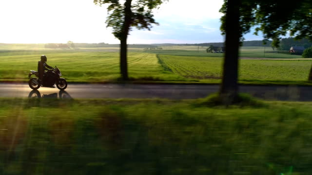 Travel by motorcycle. Rural landscape during sunset