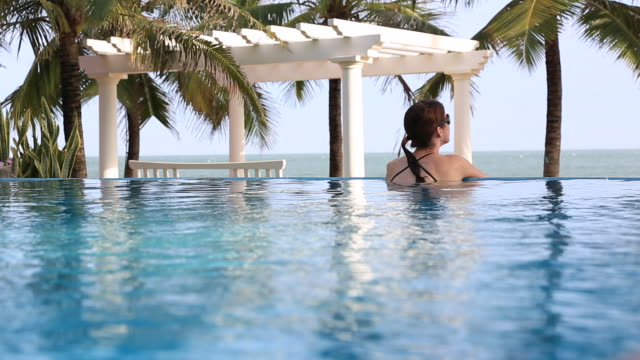 travel cinemagraph of woman relaxing inside infinity pool at tropical resort - località turistica video stock e b–roll