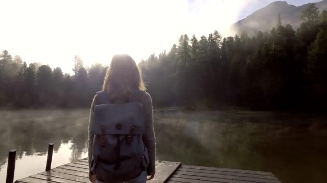 Travel female contemplating nature from lake pier, morning sunrise video