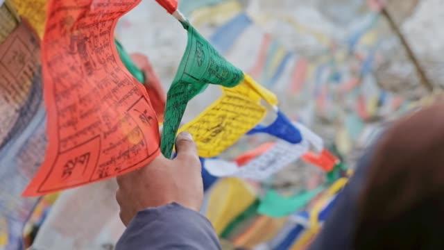 男とチベット仏教の祈りのフラグ レー ラダック インド旅行します。 - 仏塔点の映像素材/bロール