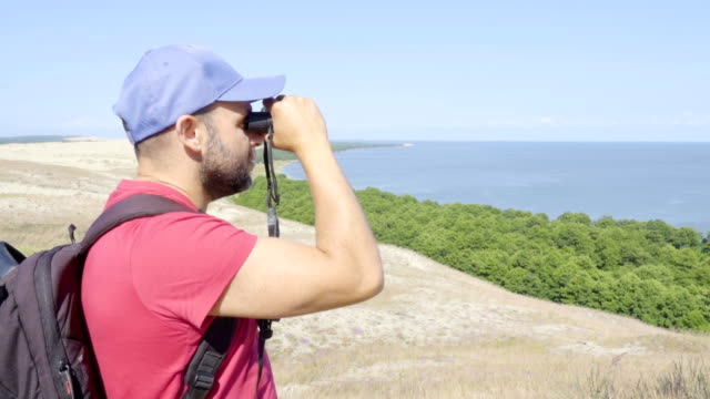 Travel man looking at wildlife with binoculars. Male on vacation looking at nature landscape. Hiker with a backpack is looking through binoculars at sea, at beautiful landscape. Mountain. Beach. video
