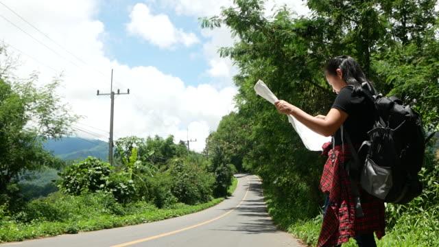vídeos y material grabado en eventos de stock de viajar mujer mochilero con mapa por la carretera durante el viaje de vacaciones de verano en la naturaleza del paisaje increíble en tailandia. conceptos de viaje y autoestopismo. - espalda humana