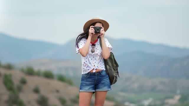 reisefrau mit rucksack fotografieren natürliche landschaft verwenden kamera. aufnahme mit red-kamera in 4k - strohhut stock-videos und b-roll-filmmaterial