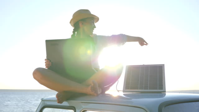 travel, young woman sitting on vintage car in sunlight using powered by battery for computer on background beach video