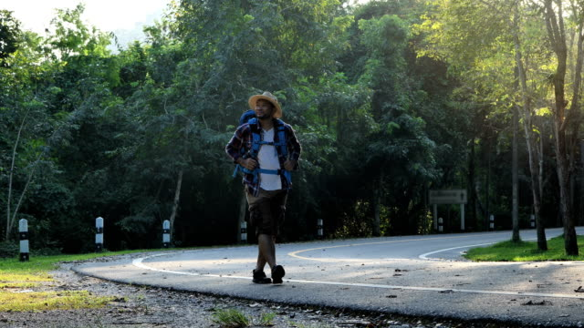 Traveler Asian men walking on road enjoying view sunset in beautiful forest landscape. Travel Lifestyle concept vacations into the wild wearing cozy shirt,hat with backpack. video 4k  Slow motion video