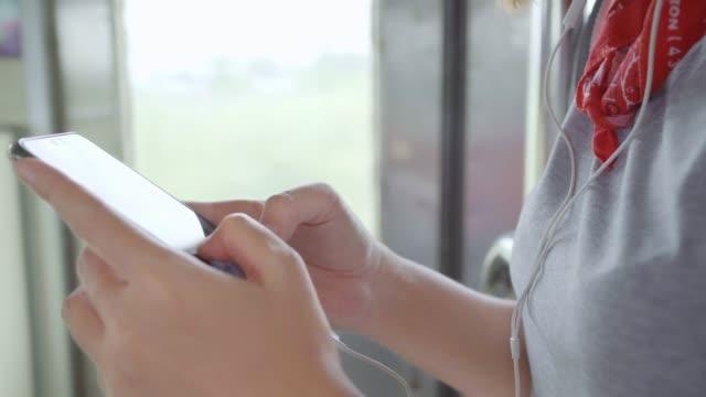 トラベラーアジアの女性スマートフォンリスニング音楽を使用して電車を取っている間にリラックス。 - 列車点の映像素材/bロール