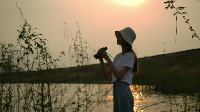 vídeos de stock e filmes b-roll de traveler asian woman with binoculars adventure in the forest mountain river lake at sunset, happy travel get the atmosphere nature outdoors. super slow motion c4k cinematic camera footage - gmail