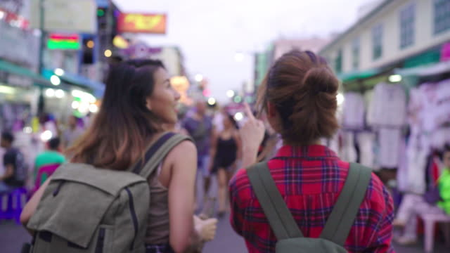 traveler backpacker asian women lesbian lgbt couple travel in bangkok, thailand. female drinking alcohol or beer at the khaosan road the most famous street in bangkok. - ночной рынок стоковые видео и кадры b-roll