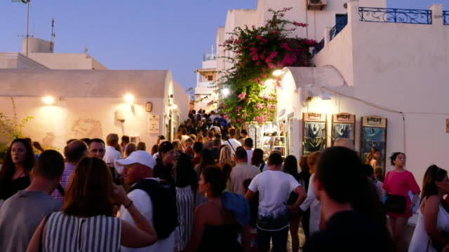 traveler crowd at fira (thira) town streets, santorini island, greece, 4k resolution. - fire filmów i materiałów b-roll