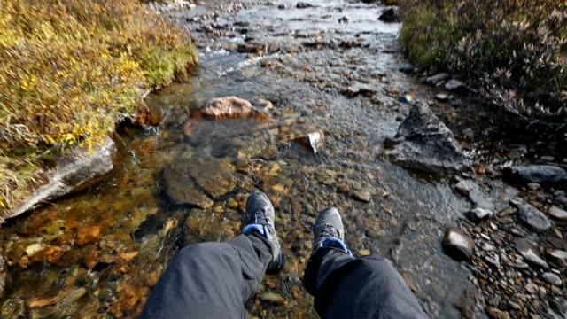 Traveler hanging leg on riverside in autumn wilderness at national park