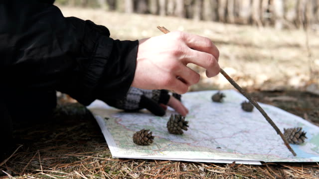 Traveler in the forest paves the route on the map - vídeo
