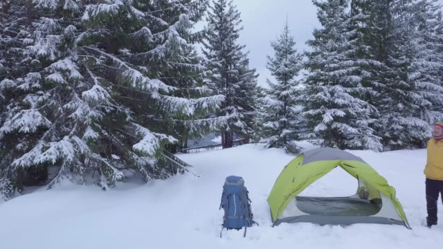 Traveler near a tent in the mountains