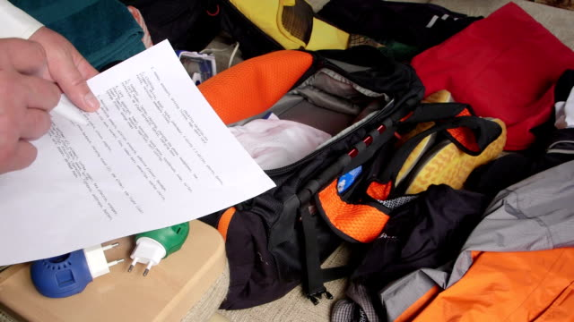 Traveler packing a bag with checklists for summer vacations and travel video