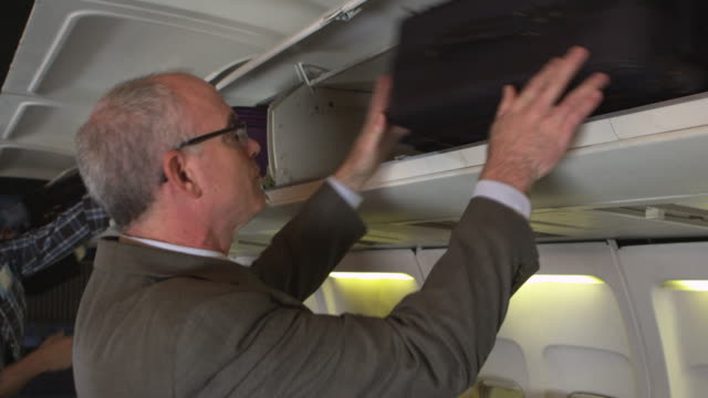 Traveler putting luggage in overhead bin video