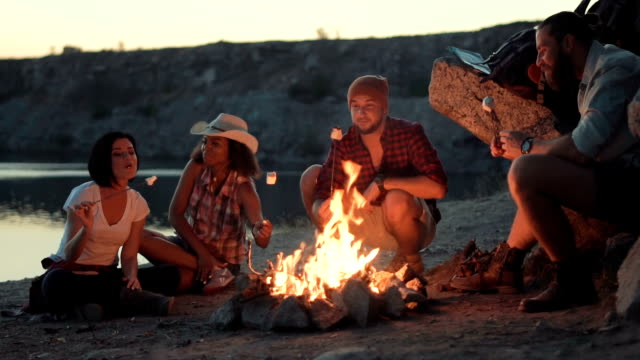 Traveler relaxing at bonfire on shore - video