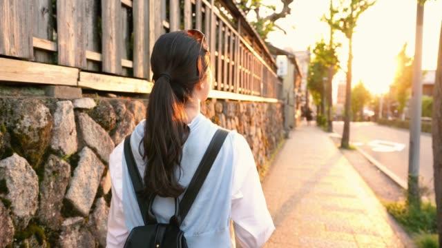 resenären ser vacker solnedgång medan promenader - walking home sunset street bildbanksvideor och videomaterial från bakom kulisserna