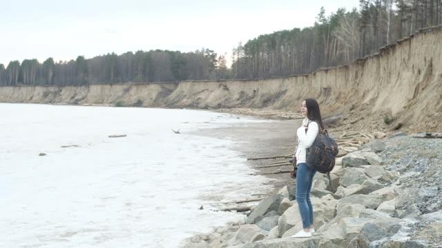 vídeos de stock, filmes e b-roll de viajante senta-se nas rochas na costa e toma uma paisagem de câmera retrô vintage - comodidades para lazer