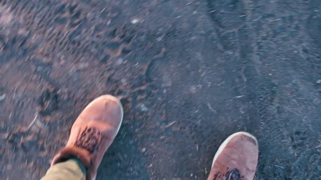 vidéos et rushes de un voyageur fait des pas dans des bottes sur de la boue gelée. - bottes