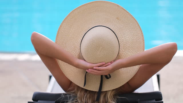 traveler tourist bikini woman girl in hat relaxing vacation happy holiday at luxury hotel tropical resort swimming pool