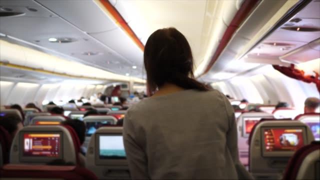 vídeos de stock, filmes e b-roll de viajante, percorrendo o avião - interior