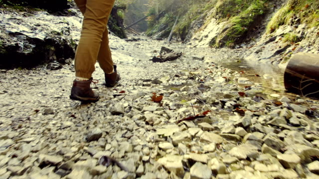 vídeos de stock e filmes b-roll de traveler walks along the mouth of  shallow mountain river. - bota