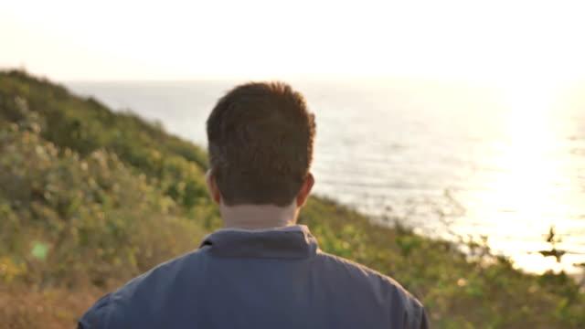 vidéos et rushes de voyageur gilet marche au sommet d'une montagne proche de l'océan. - prise avec un appareil mobile