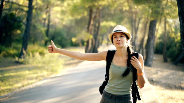 Traveler woman hitchhiking on a sunny forest road. Tourist girl looking for ride to start her journey video