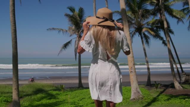 vídeos y material grabado en eventos de stock de mujer viajera va a la playa del océano - espalda humana