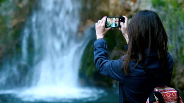vidéos et rushes de voyageur femme prise photo de cascade étonnante - photophone