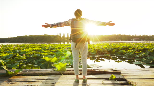 Traveler wth arm outstretched. Happy young woman enjoying traveling and every life moment. She is surrounded by a beautiful sunlight and idyllic view. life balance stock videos & royalty-free footage