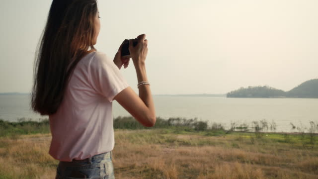 vídeos de stock e filmes b-roll de traveler young asian woman take a photo with film camera in the forest mountain river lake at sunset, happy travel nature outdoors. super slow motion c4k cinematic camera footage - gmail
